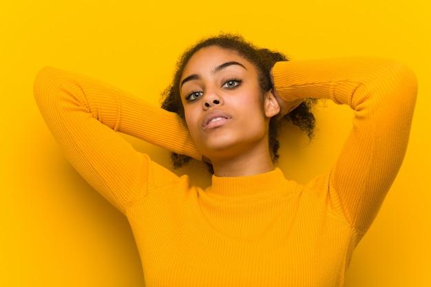 Giovane primo piano della donna di colore sopra una parete arancione