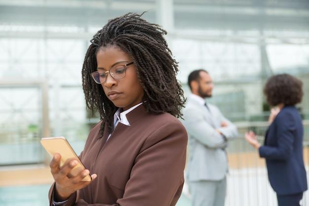 Giovane professionista concentrato che per mezzo del telefono cellulare