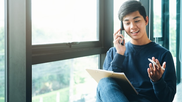 Giovane professionista di giovane impresa che parla con cliente sul suo cellulare.