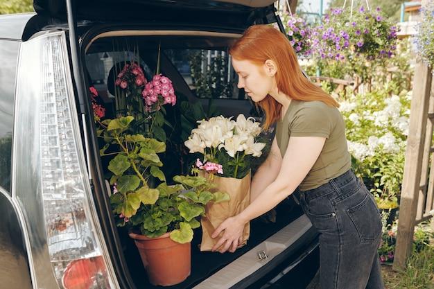 Giovane proprietario del negozio di fiori che imballa i fiori nel bagagliaio della macchina dalla serra durante il trasporto dei fiori al negozio