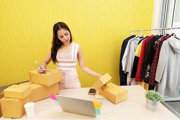 Giovane proprietario di piccola impresa startup che controlla l'indirizzo del cliente sulla scatola in posto di lavoro.