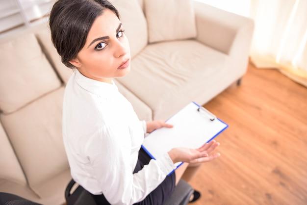 Giovane psicologa bruna che è pronta a prendere appunti.