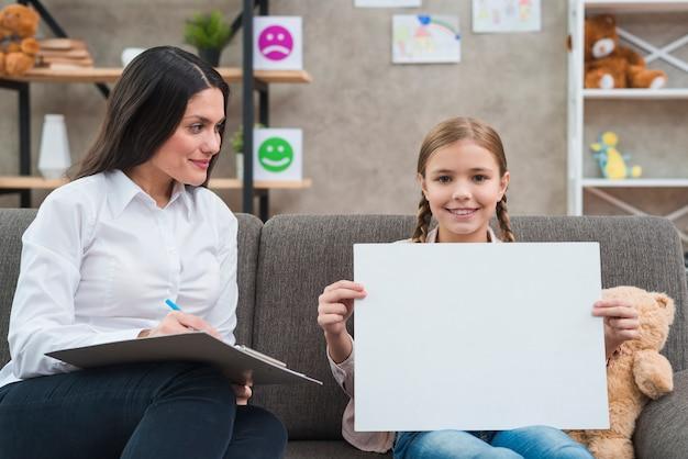 Giovane psicologo femminile che esamina bambina che mostra libro bianco in bianco alla macchina fotografica