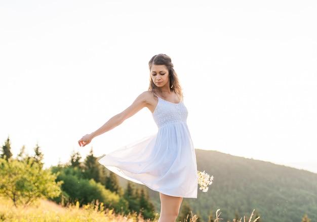 Giovane ragazza abbastanza romantica con bouquet di fiori di campo sullo sfondo del cielo blu