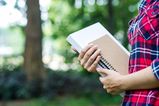 Giovane ragazza abbraccia il suo libro nella giungla verde