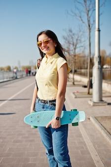 Giovane ragazza adolescente con piccolo skateboard, penny board, indossare maglietta gialla, jeans e occhiali da sole.