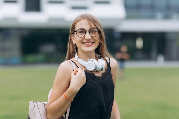 Giovane ragazza adolescente dello studente che sorride sulla via urbana. ritratto di ragazza felice che sorride sulla strada urbana.