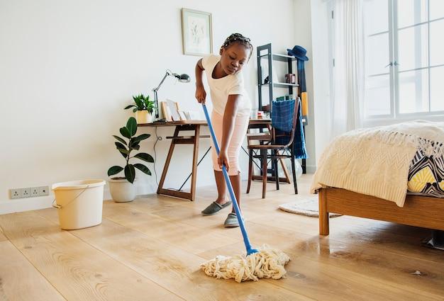 Giovane ragazza adolescente spazzare il pavimento
