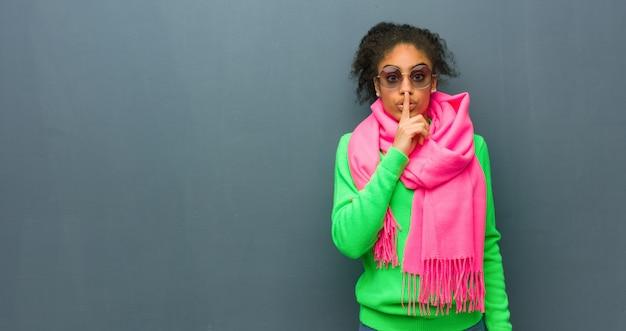 Giovane ragazza afroamericana con gli occhi azzurri che mantiene un segreto o che chiede il silenzio