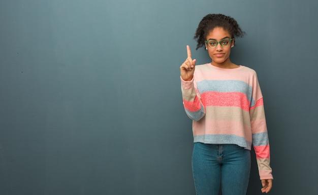 Giovane ragazza afroamericana con gli occhi azzurri che mostra il numero uno