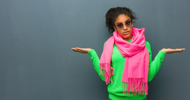 Giovane ragazza afroamericana con gli occhi azzurri confusi e dubbiosi