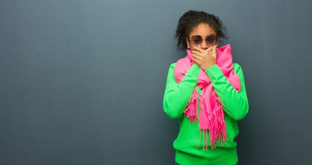 Giovane ragazza afroamericana con gli occhi azzurri sorpresa e scioccata
