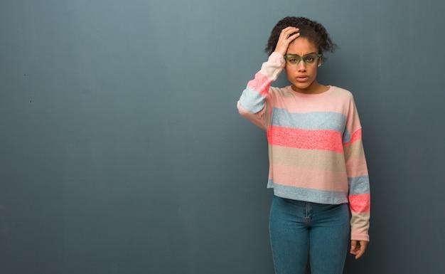 Giovane ragazza afroamericana con gli occhi azzurri stanchi e molto assonnati