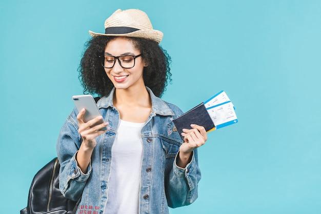 Giovane ragazza afroamericana felice sorpresa isolata su fondo blu in studio. concetto di viaggio. tenere il passaporto, i biglietti per la carta d'imbarco. usando il telefono.