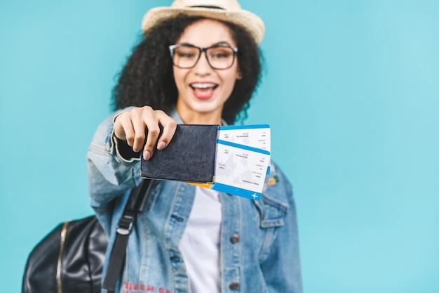 Giovane ragazza afroamericana felice sorpresa isolata su fondo blu in studio. concetto di viaggio. tenere il passaporto, i biglietti per la carta d'imbarco.