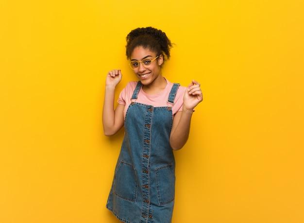 Giovane ragazza afroamericana nera con gli occhi azzurri che ballano e che si divertono