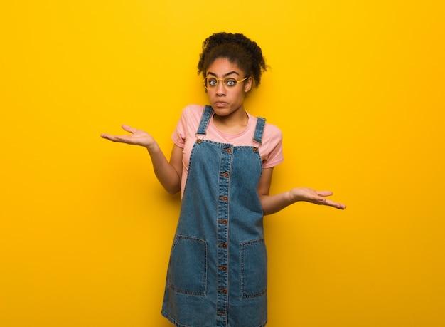 Giovane ragazza afroamericana nera con gli occhi azzurri che dubitano e che scrolla le spalle le spalle