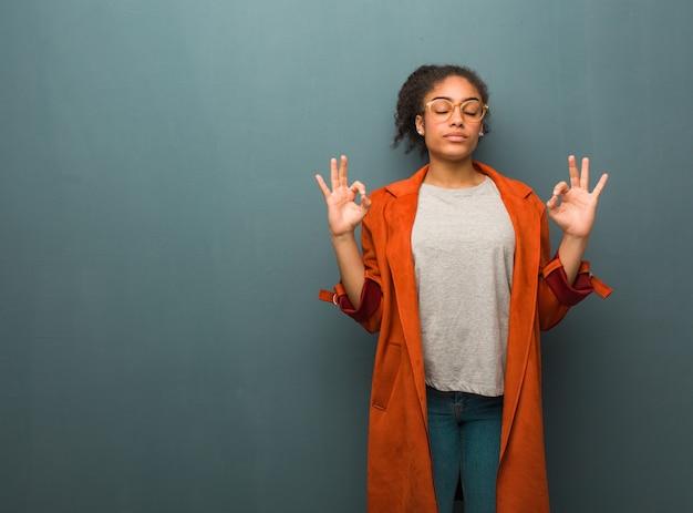 Giovane ragazza afroamericana nera con gli occhi azzurri che eseguono yoga