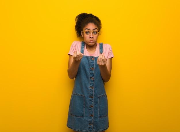 Giovane ragazza afroamericana nera con gli occhi azzurri che fa un gesto del bisogno