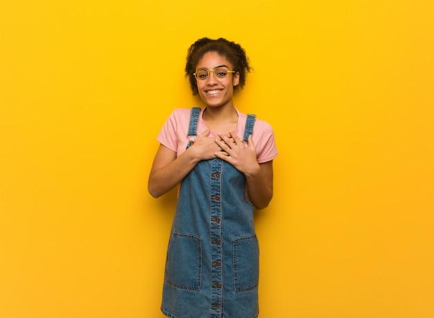 Giovane ragazza afroamericana nera con gli occhi azzurri che fa un gesto romantico