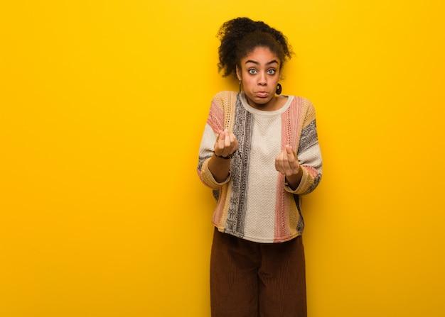 Giovane ragazza afroamericana nera con gli occhi azzurri che fanno un bisogno di gesto
