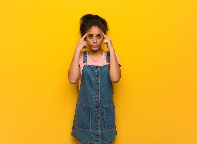 Giovane ragazza afroamericana nera con gli occhi azzurri che fanno un gesto di concentrazione