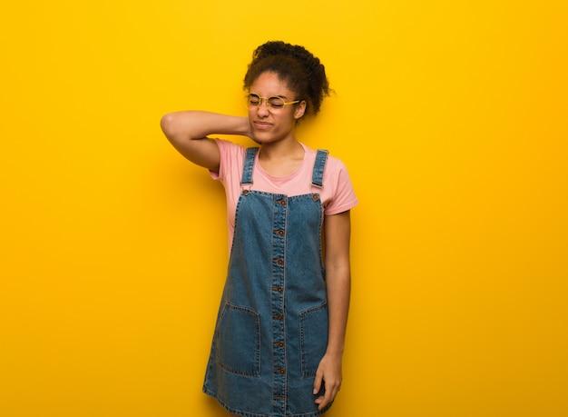 Giovane ragazza afroamericana nera con gli occhi azzurri che soffrono dolore al collo