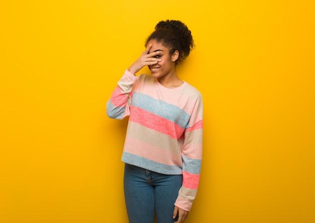 Giovane ragazza afroamericana nera con gli occhi azzurri in imbarazzo e ridendo allo stesso tempo