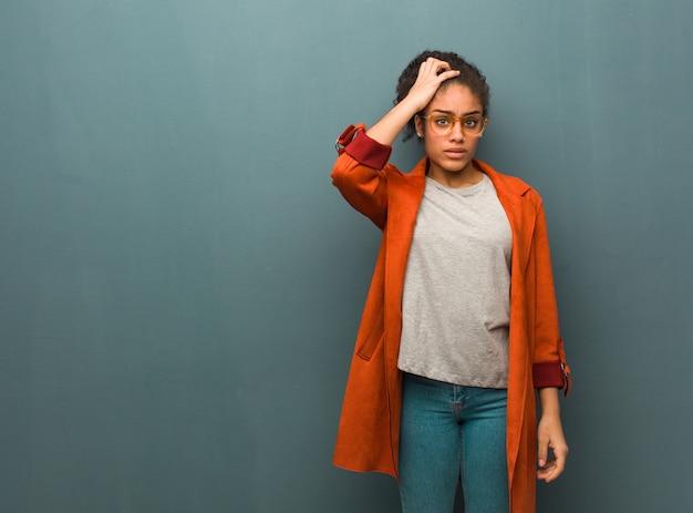 Giovane ragazza afroamericana nera con gli occhi azzurri preoccupati e sopraffatti