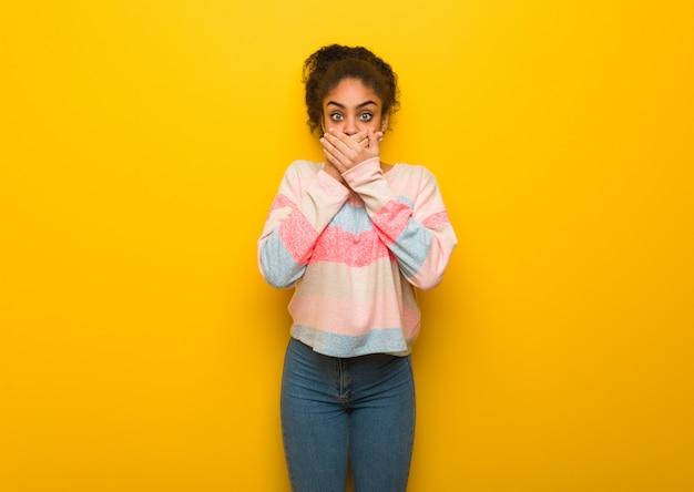 Giovane ragazza afroamericana nera con gli occhi azzurri sorpresa e scioccata