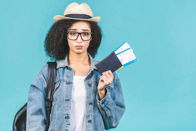 Giovane ragazza afroamericana triste isolata su fondo blu in studio. concetto di viaggio. tenere il passaporto, i biglietti per la carta d'imbarco.