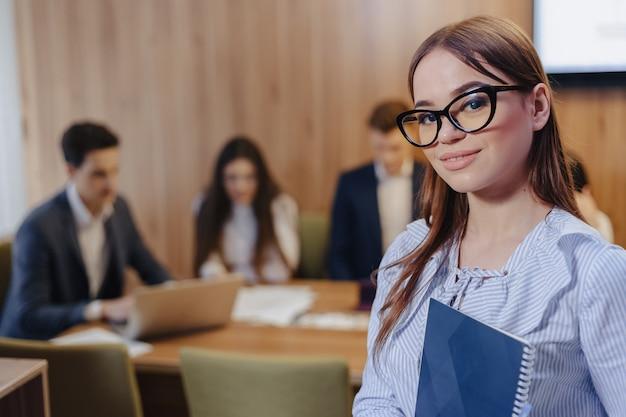 Giovane ragazza alla moda attraente di impiegato in vetri con un taccuino nelle mani su priorità bassa dei colleghi di lavoro