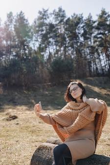 Giovane ragazza alla moda attraente sulla natura sul muro della foresta con un telefono in una giornata di sole a scattare foto di se stessa. vacanze all'aperto e dipendenza dalla tecnologia.