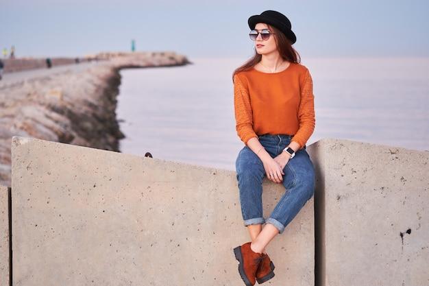Giovane ragazza alla moda che si siede in un porto marittimo