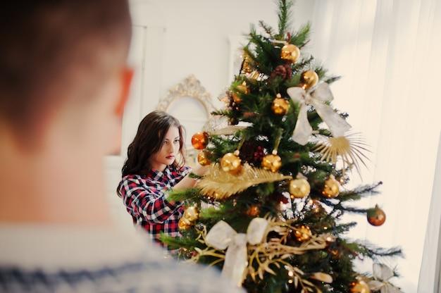 Giovane ragazza alla moda con regali di natale e decorazioni di capodanno