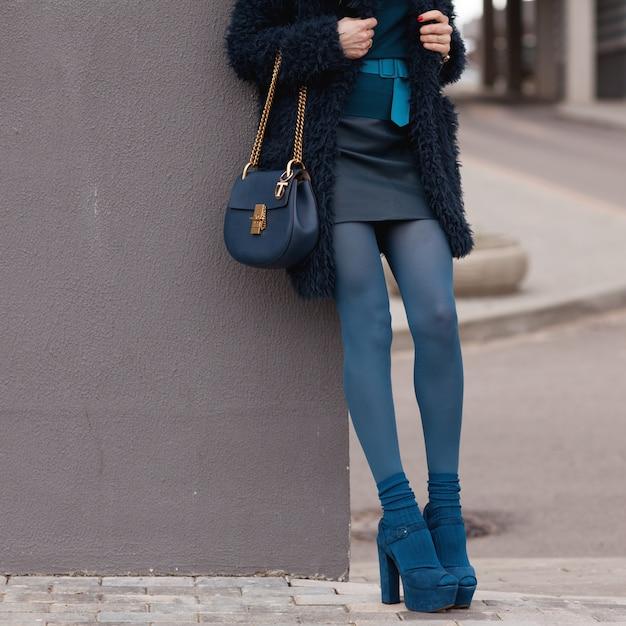 Giovane ragazza alla moda in cappotto blu e vestiti blu in posa