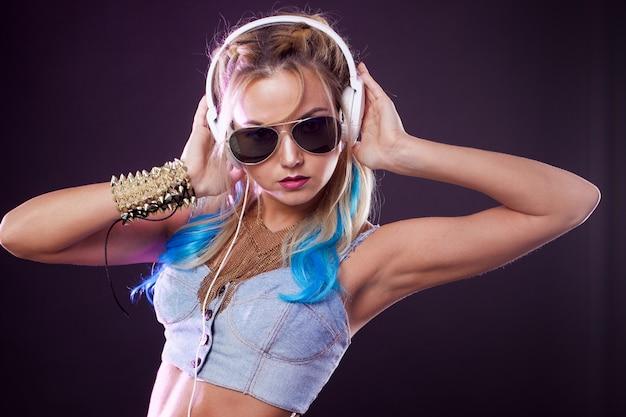 Giovane ragazza alla moda in stile discoteca. ascoltare musica e divertirsi. stile retrò