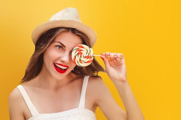Giovane ragazza alla moda in un cappello di paglia con una lecca-lecca arcobaleno su uno sfondo giallo