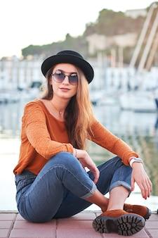 Giovane ragazza alla moda in un porto marittimo