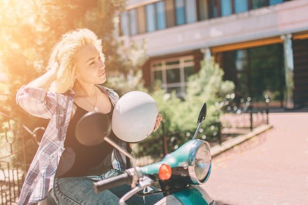 Giovane ragazza allegra che guida motorino dentro in città