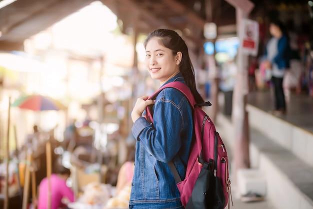 Giovane ragazza asiatica che cammina al mercato di galleggiamento di saduak di dumonoe, tailandia