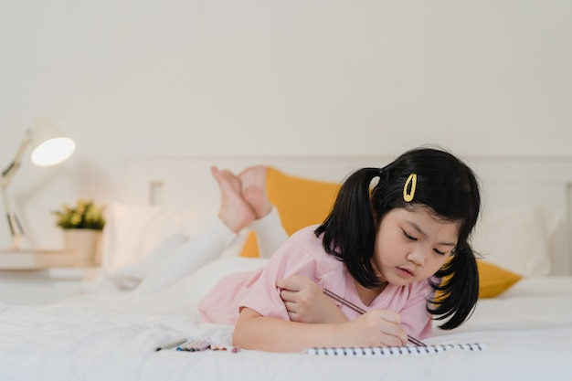Giovane ragazza asiatica che disegna a casa. il bambino giapponese del bambino della donna dell'asia si rilassa il fumetto felice di tiraggio di divertimento di resto in sketchbook prima di dormire la menzogne sul letto, ritiene la comodità e la calma in camera da letto al concetto di notte.