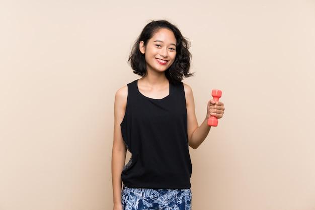 Giovane ragazza asiatica che fa sollevamento pesi sopra la parete isolata che sorride molto