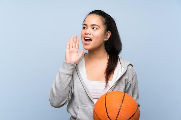 Giovane ragazza asiatica che gioca pallacanestro sopra fondo isolato che grida con la bocca spalancata