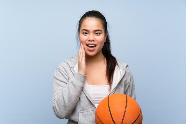 Giovane ragazza asiatica che gioca pallacanestro sopra fondo isolato con espressione facciale sorpresa e colpita