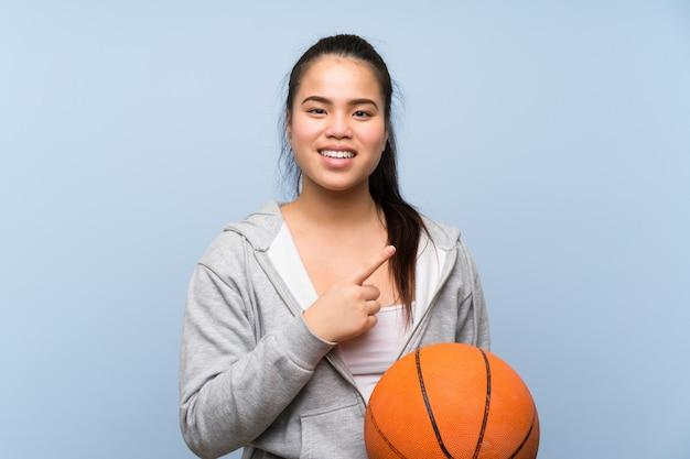 Giovane ragazza asiatica che gioca pallacanestro sopra la parete isolata che indica il lato per presentare un prodotto