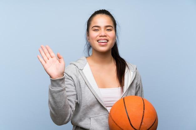 Giovane ragazza asiatica che gioca pallacanestro sopra la parete isolata che saluta con la mano con l'espressione felice