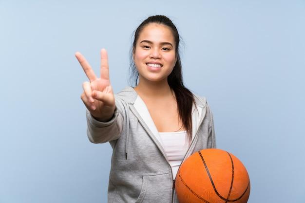 Giovane ragazza asiatica che gioca pallacanestro sopra la parete isolata che sorride e che mostra il segno di vittoria