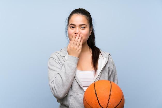 Giovane ragazza asiatica che gioca pallacanestro sopra la parete isolata con espressione facciale di sorpresa