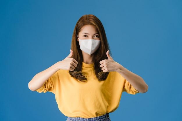Giovane ragazza asiatica che indossa la maschera facciale medica che mostra il pollice in su con vestito in un panno casual e guarda la telecamera isolata su sfondo blu. autoisolamento, allontanamento sociale, quarantena per il virus corona.